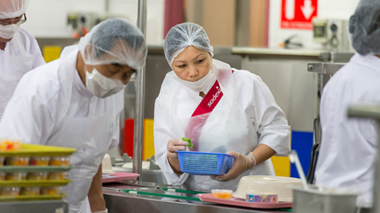 Sodexo catering employees working in a kitchen wearing hair nets and face masks