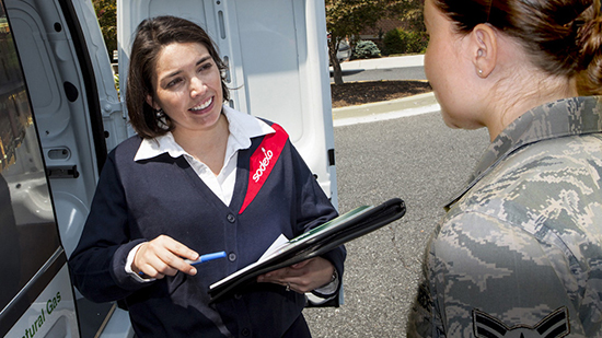 A sodexo employee speaking to an armed forces employee holding a clipboard