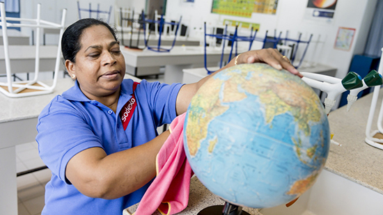 A sodexo employee cleaning a globe in a school classroom